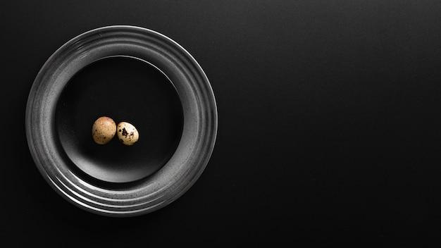 Placa escura com ovos em um fundo escuro Foto gratuita