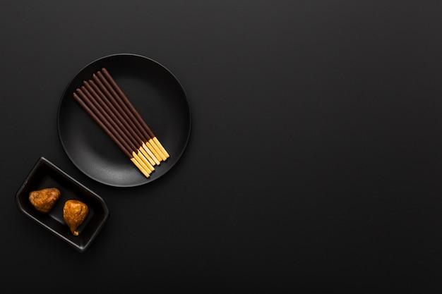 Placa escura com palitos de chocolate em um fundo escuro Foto gratuita
