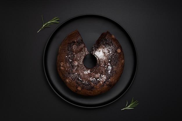 Placa escura com um bolo de chocolate em um fundo preto Foto gratuita