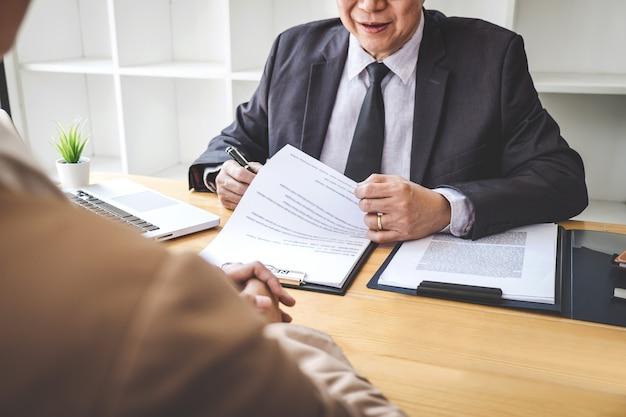 Placa lendo um currículo durante uma entrevista de emprego, empregador entrevistando um jovem candidato a emprego feminino Foto Premium