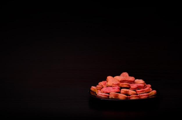 Placa preta com biscoitos vermelhos em forma de coração em uma tabela preta, dia dos namorados. vista lateral, copyspace Foto Premium