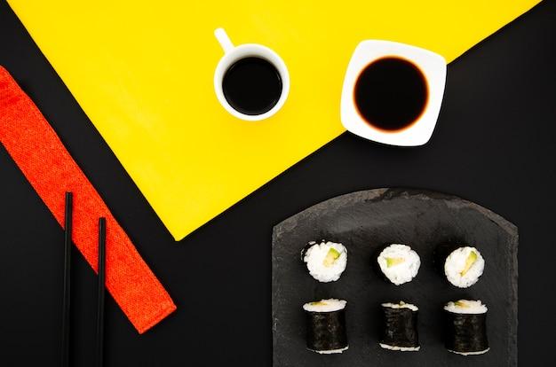Placa preta com sushi e molho de soja em um fundo preto Foto gratuita