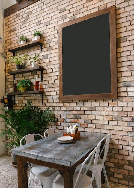 Placa preta vazia na parede de tijolo e na tabela de dinning dentro abaixo. Foto Premium