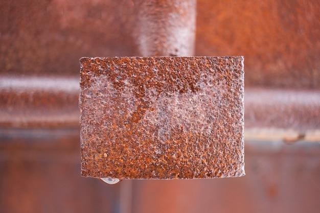 Placa retangular de metal molhado enferrujado no meio do quadro. Foto Premium