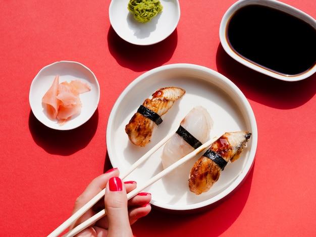 Placas brancas com sushi e wasabi em um fundo vermelho Foto gratuita