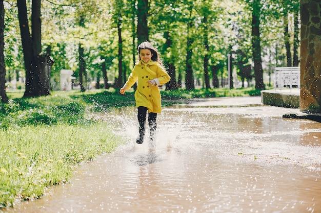 Plaiyng bonito da menina em um dia chuvoso Foto gratuita