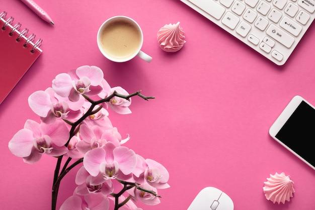 Planejamento de comemoração: cartões de telefone celular, teclado, café e convites com orquídeas em papel rosa Foto Premium
