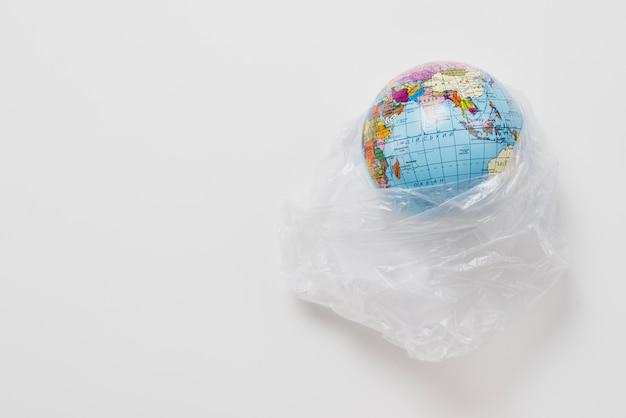 Planeta em saco de plástico no fundo cinza Foto gratuita
