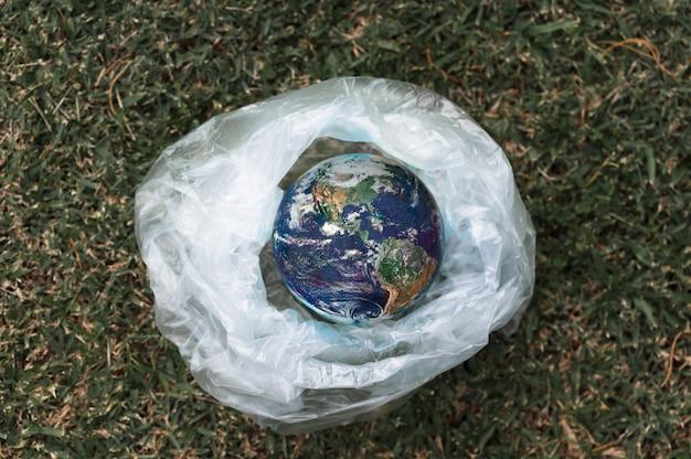 Planeta terra em um saco plástico, aquecimento global devido ao efeito estufa planeta terra em um saco plástico. o conceito de poluição por detritos plásticos Foto Premium