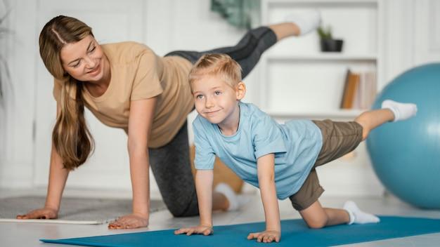 Plano completo de mulher e criança fazendo exercícios juntos Foto gratuita