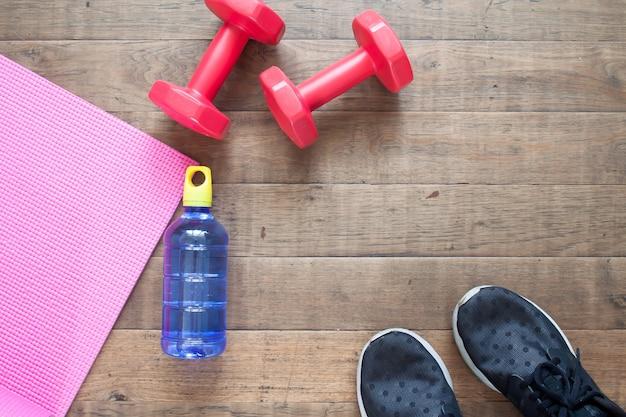 Plano criativo leigos do conceito de treino. equipamento de fitness, garrafa de água e sapatas do esporte no assoalho de madeira Foto Premium