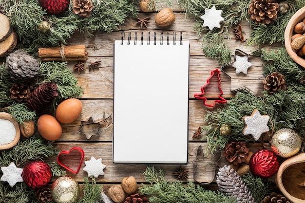 Plano de deliciosas guloseimas de natal com bloco de notas vazio Foto gratuita