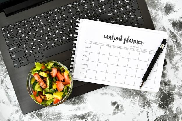 Plano de exercícios por uma semana e tigela com salada de legumes no local de trabalho perto do computador Foto Premium