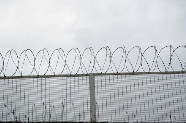 Plano de fundo de uma cerca com arame farpado sob um céu escuro Foto gratuita