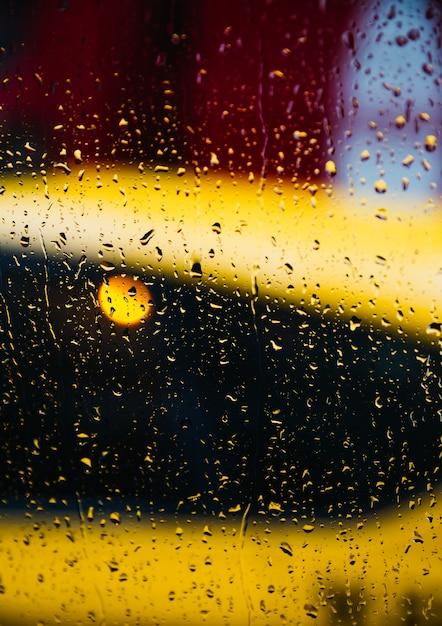 Plano de fundo desfocado da rua de nova york com gotas de água, luzes e carros na noite de chuva Foto Premium