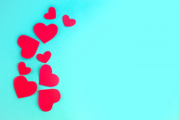 Plano de fundo dia dos namorados. corações vermelhos sobre fundo azul pastel. conceito dia dos namorados vista plana, vista superior, cópia espaço Foto Premium