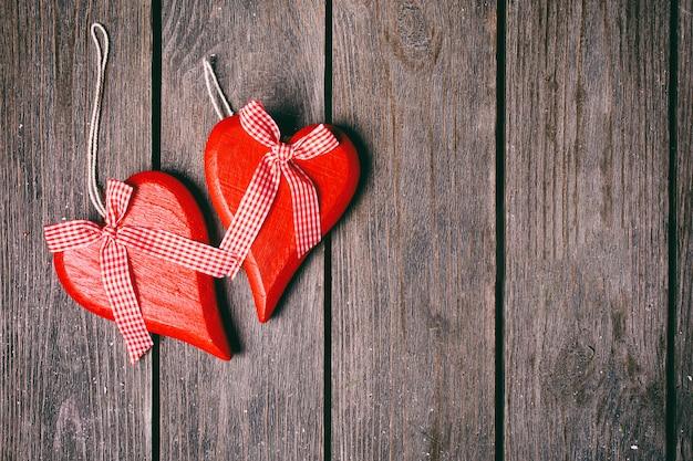 Plano de fundo dia dos namorados. par de corações vermelhos com fita quadriculada em fundo de madeira. vista do topo Foto Premium