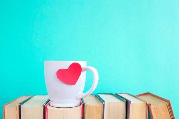 Plano de fundo dia dos namorados. xícara de café ou chá ou café sobre livros antigos Foto Premium
