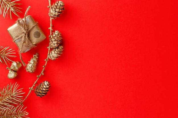 Plano de natal leigos composição no vermelho com ornamento dourado festivo no vermelho. cartão de felicitações vista superior, Foto Premium