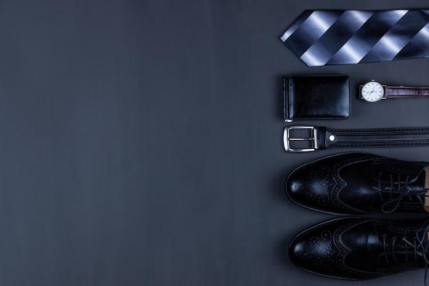 Plano de negócios plano de fundo com um espaço de cópia. sapatos masculinos, carteira de relógio de pulso, cinto, celular e uma gravata em fundo preto. Foto Premium