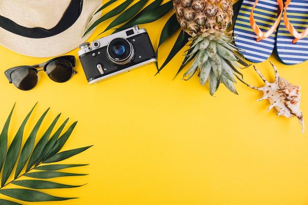 Plano de verão plano de fundo. folhas de palmeira, flip-flops, abacaxi, óculos de sol, câmera, chapéu de palha e shell em fundo amarelo. Foto Premium
