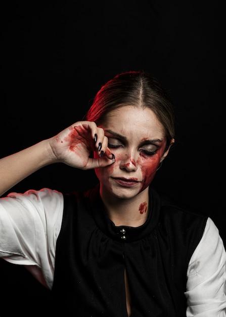 Plano médio de mulher com maquiagem sangrenta Foto gratuita