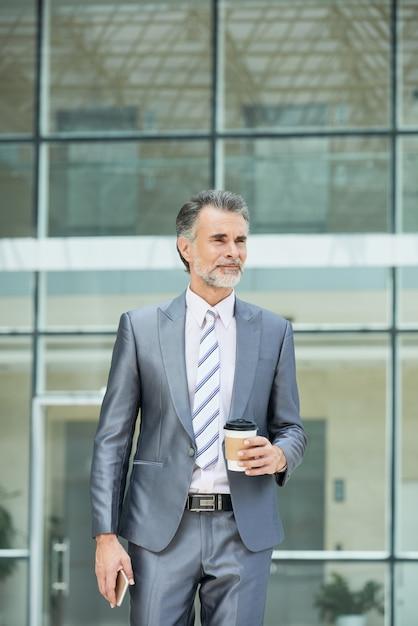 Plano médio do executivo de negócios inteligente em forlmalwear do lado de fora do prédio para tomar seu café para viagem Foto gratuita