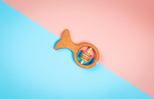 Plano minimalista colocar com um peixe chocalho de madeira de faia, sobre um fundo geométrico vibrante multicolorido isolado. Foto Premium