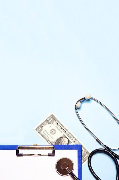 Plano vertical leigo pago remédio, suborno para tratamento. estetoscópio em um formulário de dólar e papel. vista superior, copie o espaço Foto Premium