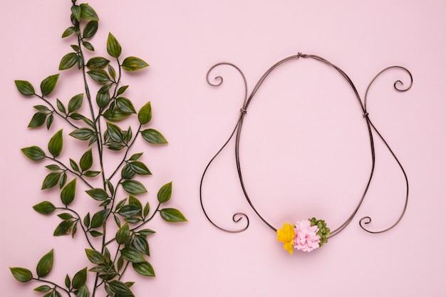 Planta verde com folhas perto do quadro oval contra o pano de fundo rosa Foto gratuita