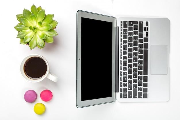 Planta verde em uma panela, xícara de café, biscoitos coloridos e laptop prata moderno sobre fundo branco Foto Premium