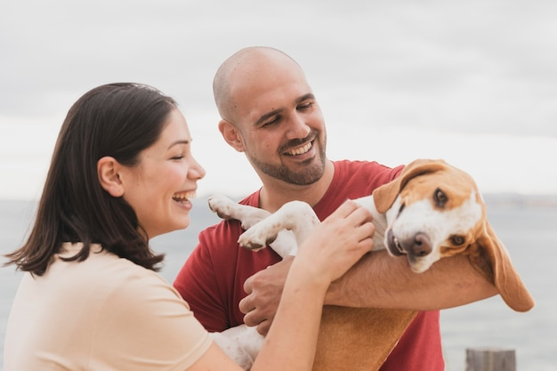 Playign de casal com cachorro ao ar livre Foto gratuita