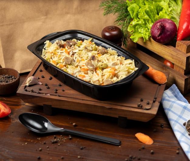Plov, guarnição de arroz com legumes, cenouras, castanhas e pedaços de carne takeaway Foto gratuita