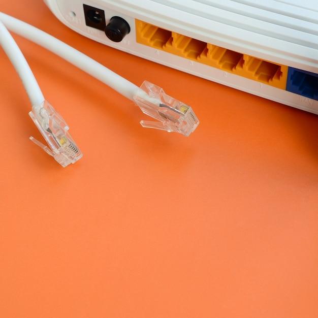 Plugues de cabo de internet e roteador de internet mentem sobre um fundo laranja brilhante. itens necessários para conexão com a internet Foto Premium