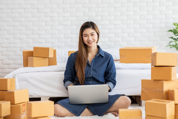 Pme empreendedor de jovens mulheres asiáticas trabalhando com laptop para compras on-line em casa Foto Premium