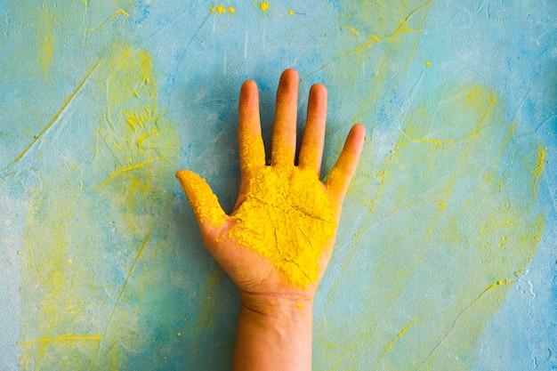 Pó amarelo na palma da mão contra a parede desarrumada pintada com cor Foto gratuita