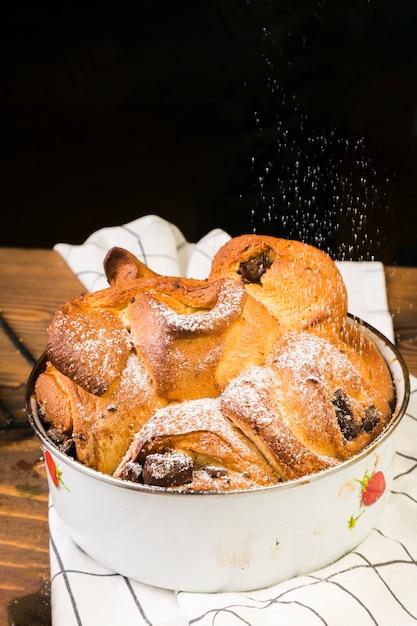Pó de açúcar polvilhado na sobremesa assada em lata no guardanapo xadrez sobre a mesa Foto gratuita