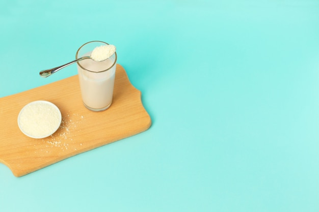Pó de colágeno e iogurte em um copo com uma colher por cima, sobre fundo azul. Foto Premium
