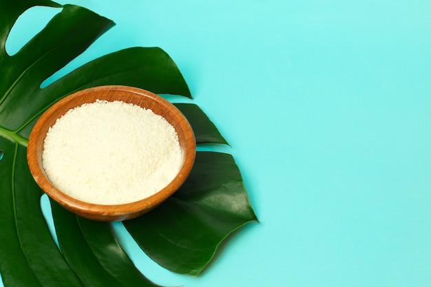 Pó de colágeno na tigela sobre fundo de folha de palmeira. Foto Premium
