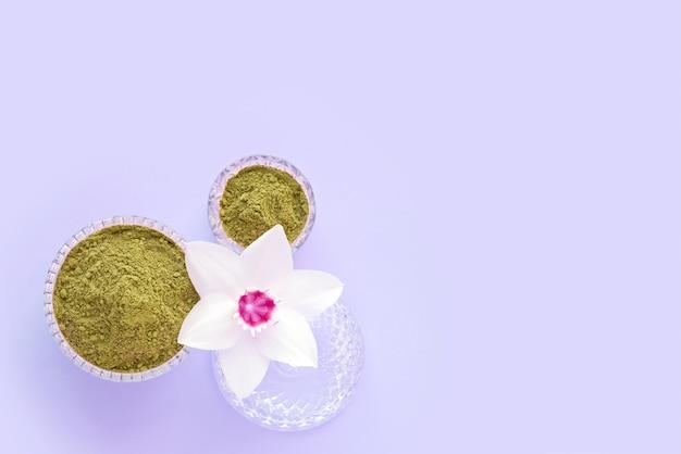 Pó de henna natural e flor branca em uma mão feminina em um fundo rosa. conceito de beleza feminina e cosmetologia. sobrancelha e coloração de cabelo. Foto Premium