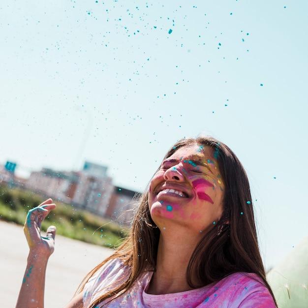 Pó de holi azul sobre a jovem sorridente ao ar livre Foto gratuita