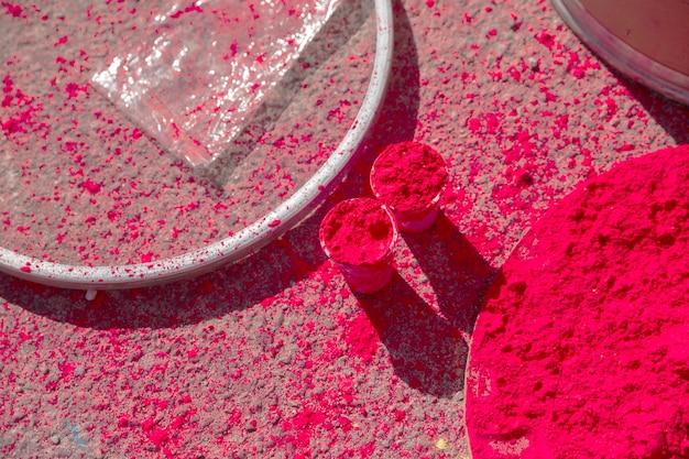 Pó de holi vermelho em copos e placa Foto gratuita