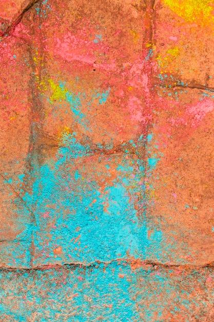 Pó multicolorido do festival de holi na calçada de tijolos vermelhos Foto gratuita