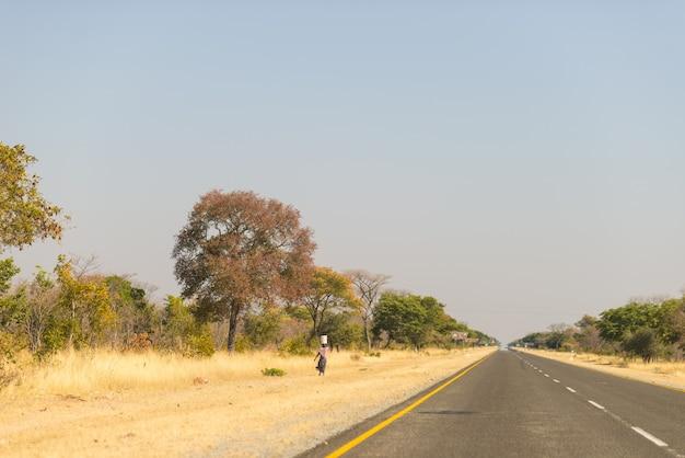 Pobre mulher caminhando na beira da estrada na zona rural de caprivi, a região mais populosa da namíbia, áfrica. Foto Premium
