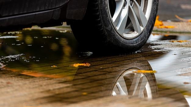 Poça na calçada com um reflexo da roda do carro e folhas coloridas de outono Foto Premium