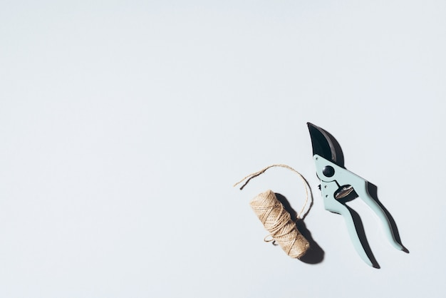 Podador de ramo e linhas de linho de artesanato sobre fundo cinza. Foto Premium