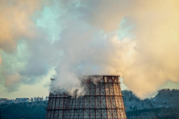 Poderosa chaminé de fábrica industrial está fumegando e emitindo dióxido de carbono no meio ambiente Foto Premium