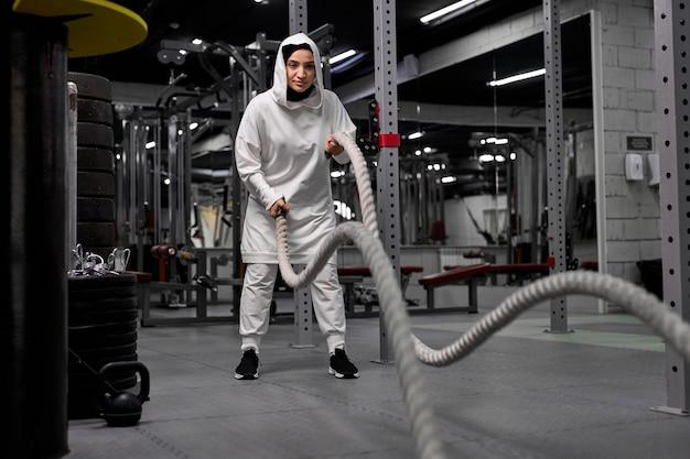 Poderosa treinadora de cross fit em hijab árabe faz treino de batalha com cordas sozinha na academia, concentrada em exercícios com equipamentos esportivos Foto Premium