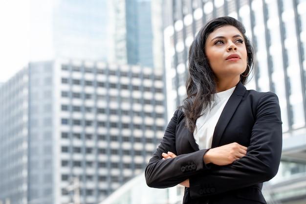 Poderoso líder de mulher de negócios latino em pé com o braço cruzado Foto Premium