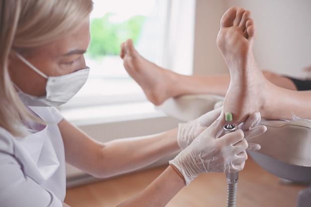 Podólogo usando equipamento de retificação e polimento de procedimento para pedicure de pés Foto Premium
